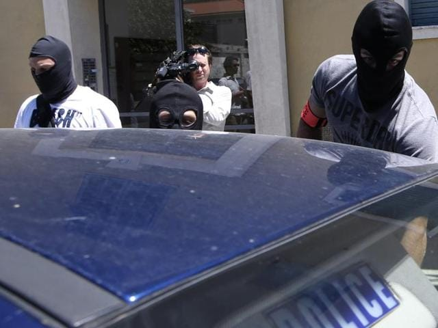 French hooded police officers leave the building where lived Mohamed Lahouaiej Bouhlel, in Nice, southern France, Saturday. The man responsible for turning a night of celebration into one of carnage in the seaside city of Nice was a petty criminal who hadn't been on the radar of French intelligence services before the attack.