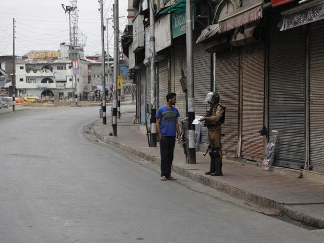 """A Kashmiri woman crosses a road past a security personnel during curfew in Srinagar, Jammu and Kashmir, Saturday, July 16, 2016.  The government banned the publication of newspapers in the Valley for three days on Saturday """"to ensure peace""""."""