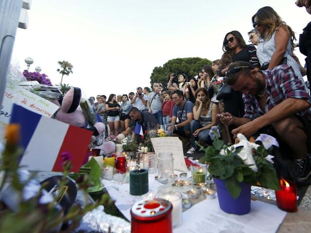 People gather near flowers and candles left in tribute to victims the day after a truck ran into a crowd at high speed killing scores and injuring more on the Promenade des Anglais who were celebrating the Bastille Day national holiday, in Nice.