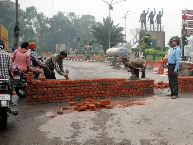 MC officials building a brick wall on the road that leads to Jagraon Bridge, which was closed to four-wheelers on Thursday. The bridge will remain shut for a year to carry out repairs.