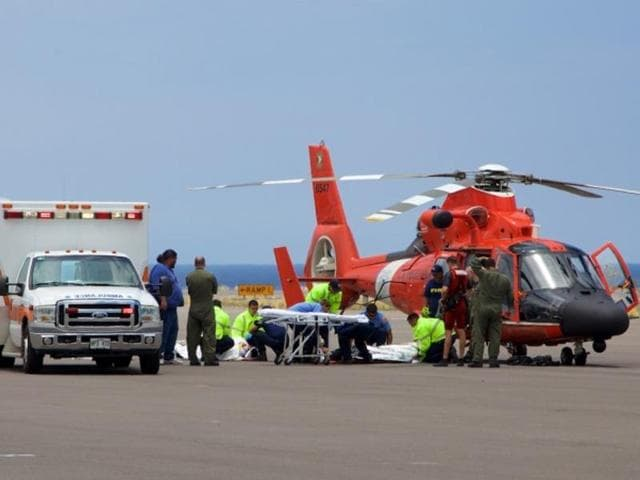 Coast Guard crew safely delivers David McMahon and Sidney Uemoto to emergency medical personnel in Kona, Hawaii on Friday, following their rescue nine miles off Kona.
