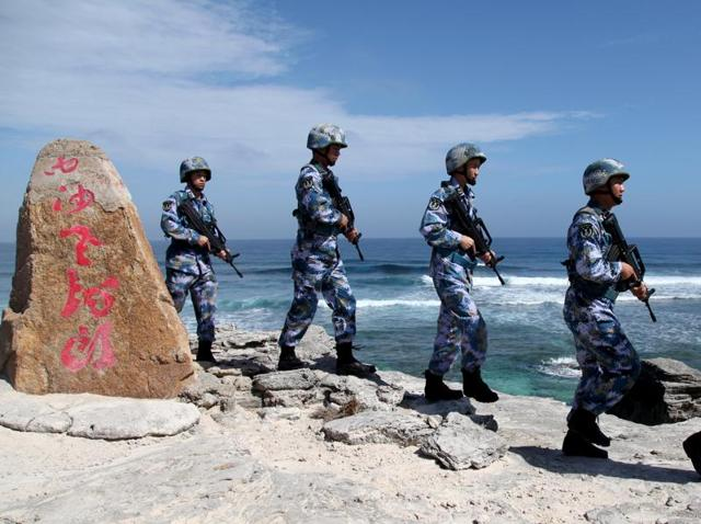 Soldiers of China's People's Liberation Army (PLA) Navy patrol at Woody Island in the Paracel Archipelago, which is known in China as the Xisha Islands, on January 29, 2016.
