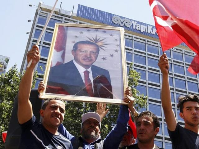 Supporters of Turkish President Tayyip Erdogan lift up his portrait as they celebrate with flags in Ankara.