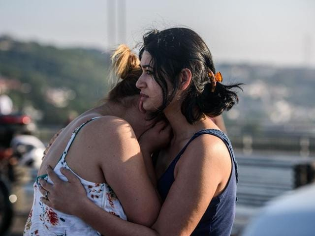 Women react after people took over military position on the Bosphorus bridge in Istanbul.