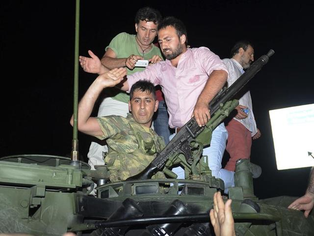 People stand on a tank after they stopped it in Istanbul, early Saturday. Members of Turkey's armed forces said they had taken control of the country, but Turkish officials said the coup attempt had been repelled early Saturday morning in a night of violence, according to state-run media.