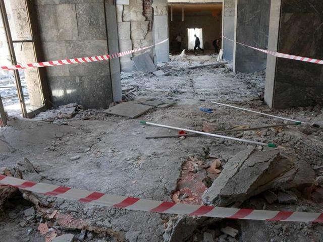 A man walks through rubble after the Grand National Assembly of Turkey was bombed by rebel jets.