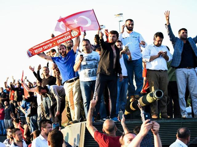 People stand and celebrate on an army tank after taking over military position on the Bosphorus bridge in Istanbul on Saturday, following an attempt by discontented soldiers to seize power from President Recep Tayyip Erdogan that claimed more than 190 lives.