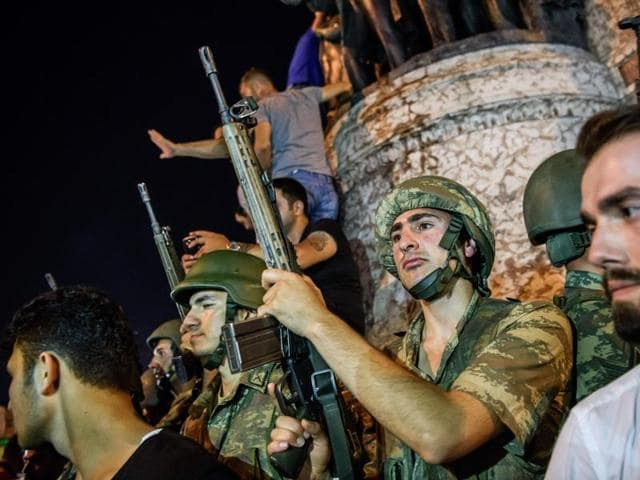 Turkish solders stay with weapons at Taksim square as people protest against the military coup in Istanbul on Saturday.