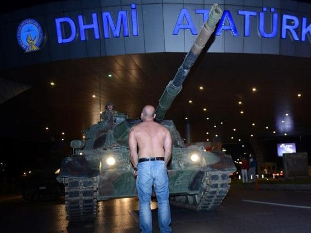 A man stands in front of a Turkish army tank at Ataturk airport in Istanbul, Turkey.