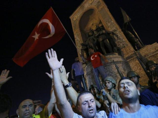 Turkish military stand guard near the the Taksim Square as peiple wave with Turkish flags in Istanbul.