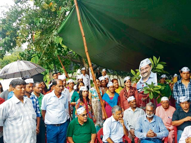 AAP workers gather outside party's state chief Anoop Nautiyal's residence in Dehradun on Sunday.
