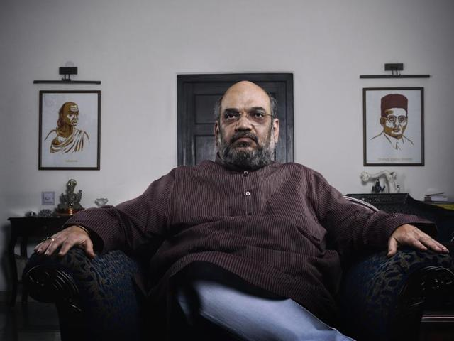 BJP president Amit Shah at his residence in New Delhi on Thursday. The senior politician draws inspiration from Chanakya and Vinayak Damodar Savarkar, whose portraits can be seen on the wall behind him.(Reuben Singh/HT Photo)