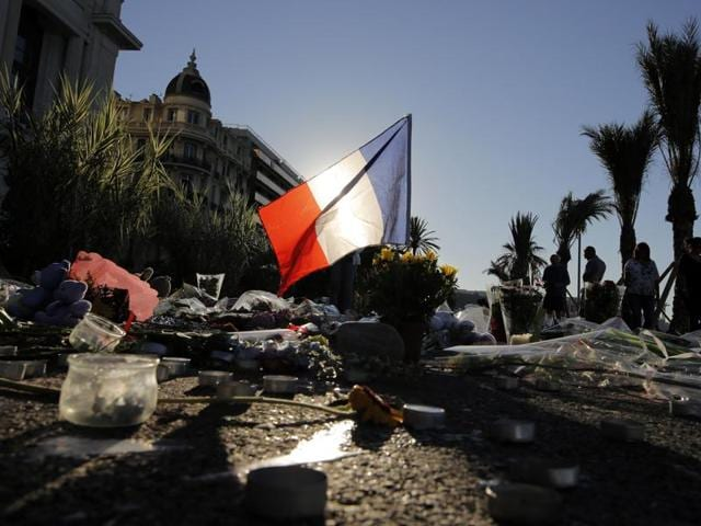 A French flag stands stall among a floral tribute for the victims killed during a deadly attack, on the famed Boulevard des Anglais in Nice, southern France.