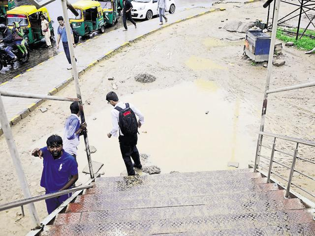 A commuter tries to hop over a puddle outside Huda City Centre metro station after the rain on Saturday.
