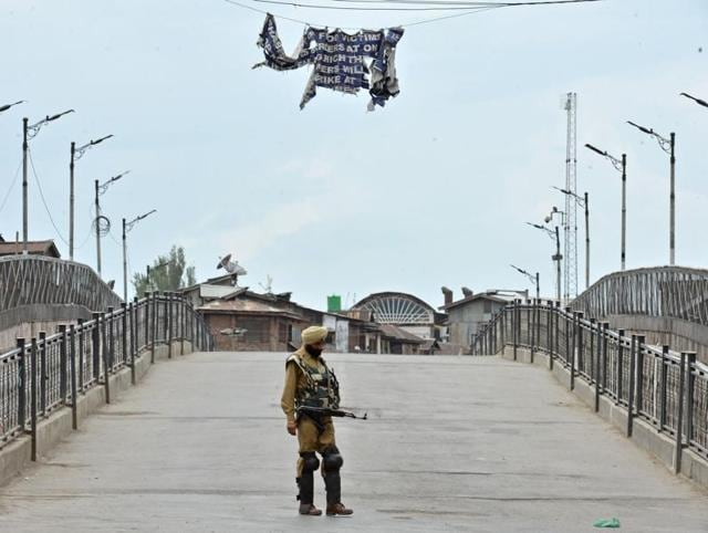 An Indian paramilitary officer stands guard during the ninth day of a curfew, in Srinagar. Curfew in Kashmir entered its ninth day on Sunday.