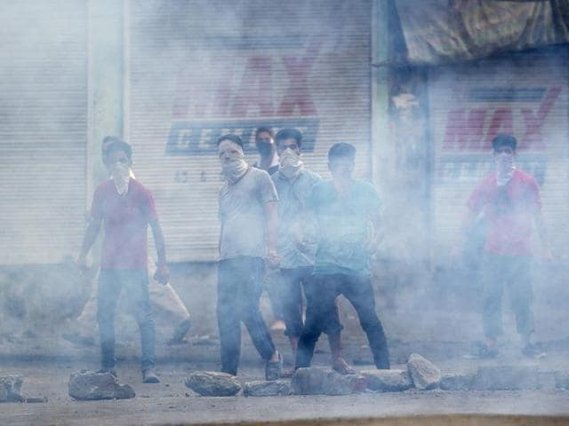 Masked protesters stands behind a screen of tear gas smoke in Srinagar, Kashmir.