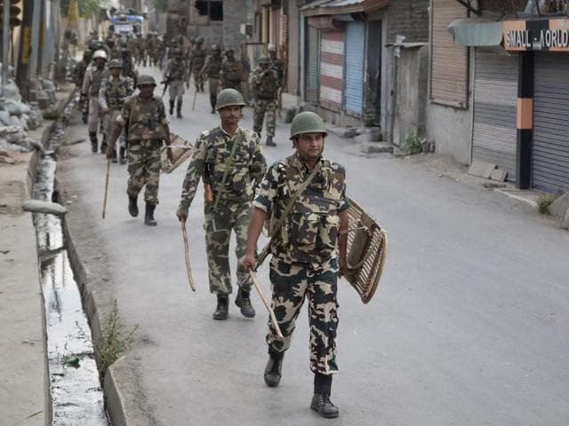 Paramilitary soldiers walk back towards their base camp during curfew in Srinagar.