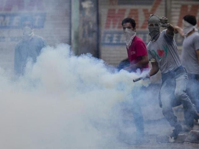 A protester holds an exploded tear gas shell to throw back at security forces as clashes continue in Srinagar.