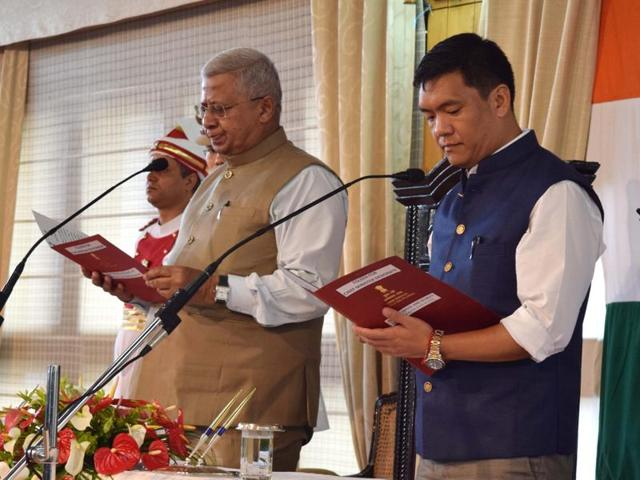 Tripura governor Tathagata Roy administers the oath of office and secrecy to Pema Khandu (right) on Sunday.