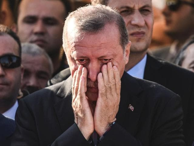 Turkey's President Recep Tayyip Erdogan reacts after attending the funeral of a victim of the coup attempt in Istanbul.