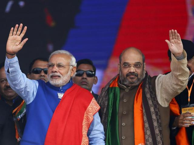 Prime Minister Narendra Modi (L) and Amit Shah, the president of the ruling Bharatiya Janata Party (BJP), wave to their supporters during a campaign rally in New Delhi.