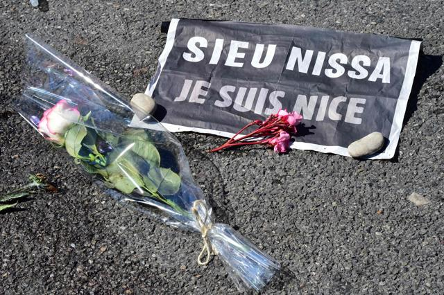 A newly wed couple places flowers at a makeshift memorial on the pavement at the Promenade des Anglais in Nice on Saturday in tribute to the victims of the deadly Bastille Day attack.