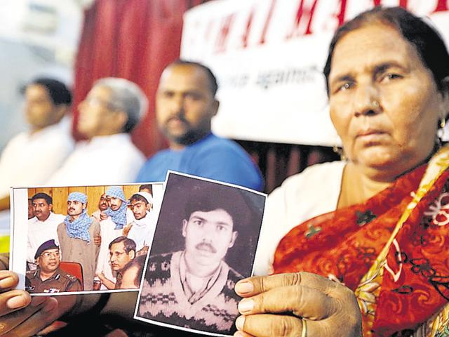 Mahesh Devi holding the photo of her son Pravin during a press meet in Lucknow recently.