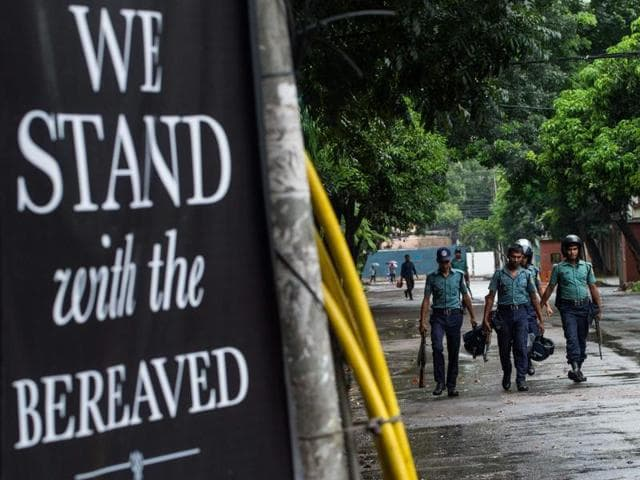 Bangladeshi policemen walk near a banner that reads