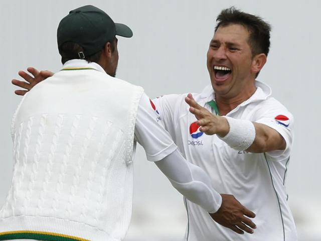 Pakistan's Yasir Shah (5L) is congratulated by team mates after taking the wicket of Jonny Bairstow .