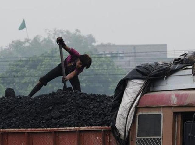 A labourer loads coal onto a truck at the Kankaria Railway Yard in Ahmedabad.