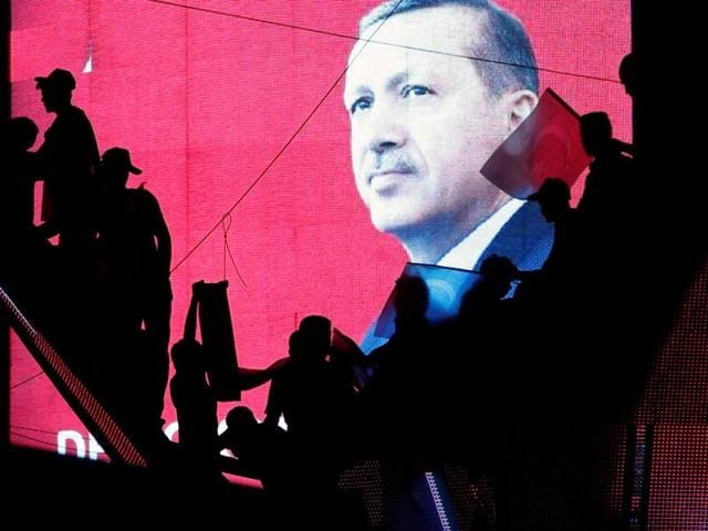 Turkish supporters are silhouetted against a screen showing President Tayyip Erdogan during a pro-government demonstration in Ankara, Turkey.