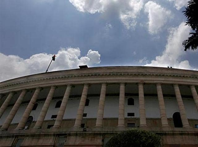 Clouds hover over the Parliament house on the opening day of the monsoon session, in New Delhi.