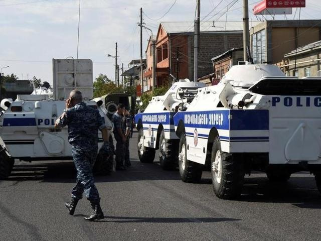Police and special forces secure the area around a police station in Yerevan, Armenia, on Sunday. Armenian security forces say a group of armed men has attacked a police station in the capital, killing one officer, wounding two and taking others hostage.