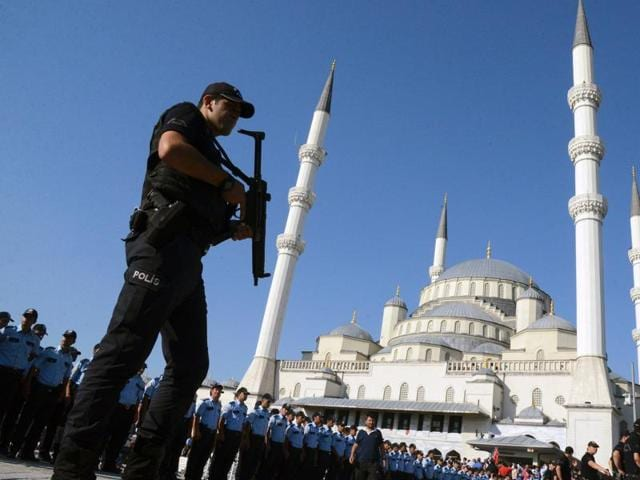 An armed Turkish police officer stands guard during a funeral ceremony for victims of the failed July 15 coup attempt at Kocatepe Mosque in Ankara.