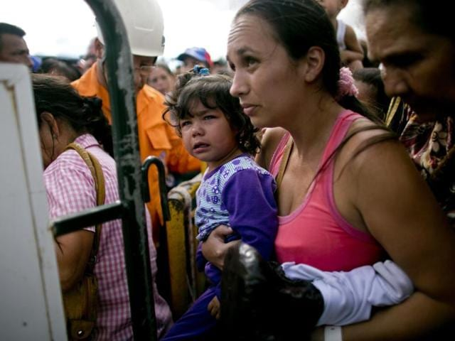 A woman carrying her daughter crosses into Colombia through the Simon Bolivar bridge in San Antonio del Tachira, Venezuela, July 17, 2016. Tens of thousands of Venezuelans crossed the border into Colombia on Sunday to hunt for food and medicine that are in short supply at home.