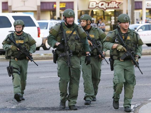 Law enforcement personnel walk near the scene where police officers were shot in Baton Rouge, Louisiana.