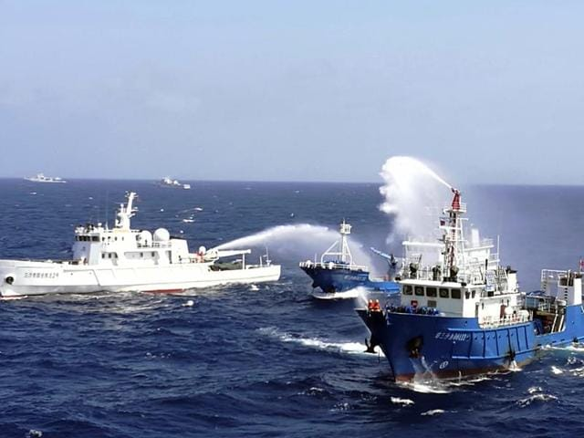 This July 14 photo shows Chinese ships putting out a fire on a mock cargo vessel during an emergency drill in the South China Sea near Sansha, in south China's Hainan province.(AFP)