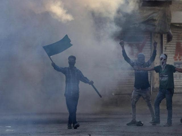 Masked Kashmiri protesters shout freedom slogans amid tear gas smoke during a protest in Srinagar.