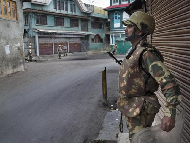 Paramilitary soldiers stand guard outside a closed market during the eleventh straight day of curfew in Srinagar.