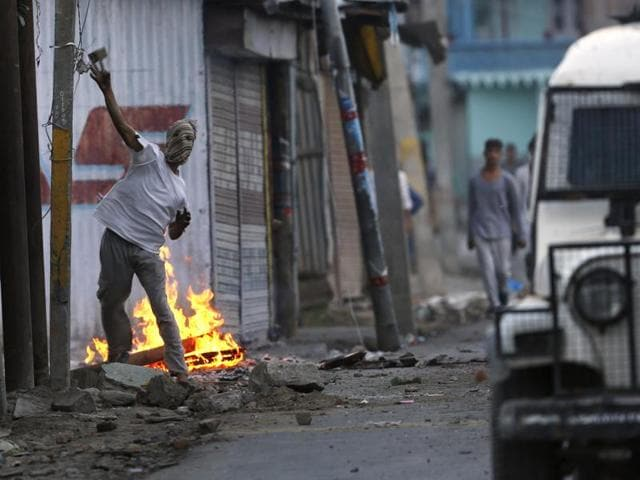 A Kashmiri protester throws a stone at a police vehicle during a protest in Srinagar.