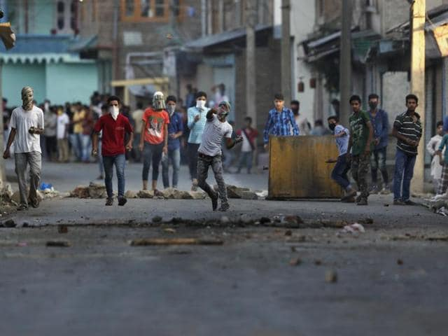 A Kashmiri protester throws a stone at Indian policemen during a protest in Srinagar, Kashmir.
