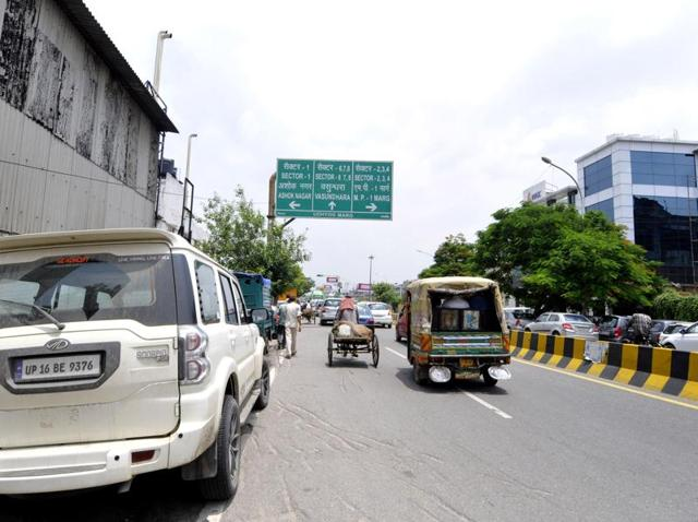 On both sides of Udyog Marg, cars, truck, bikes, autos and other vehicles can be seen parked, causing congestion.