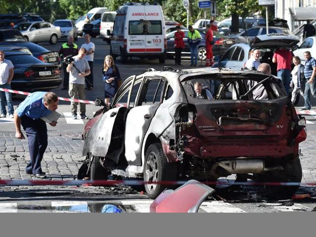 Ukrainian police officers and security services experts examine the charred car of journalist Pavel Sheremet after he was killed in a car bombing in Kiev on Wednesday. The 44-year-old, originally from Belarus but a Russian citizen who worked for Ukrainska Pravda, an independent news site, died when the explosion tore through the car.
