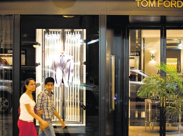 Shoppers walk past a Tom Ford International LLC store at the DLF Emporio shopping mall in New Delhi.