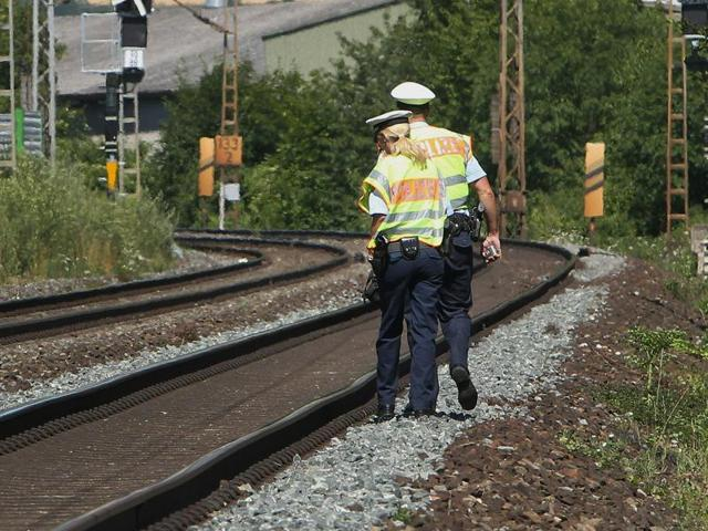 Police officers walk along train tracks in Wuerzburg southern Germany a day after a man attacked train passengers with an axe.