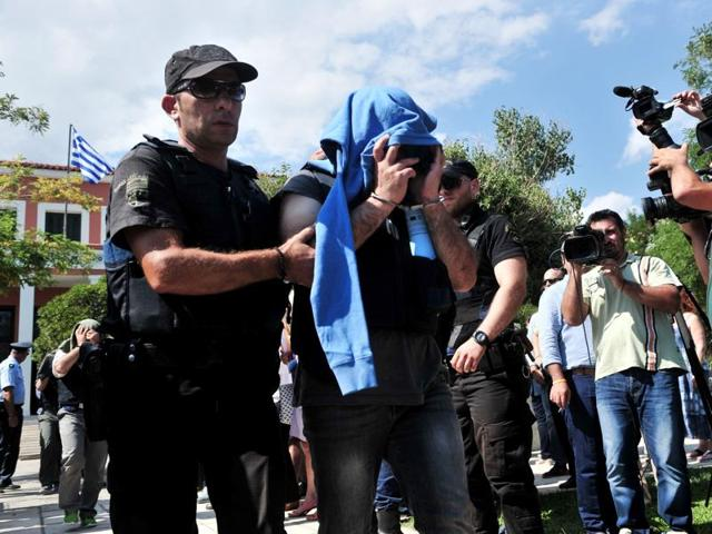 A Greek police officer escorts a Turkish officer who fled to Greece by helicopter after last week's failed coup, as he leaves the courthouse of Alexandroupoli, near the Greek-Turkish border, on July 21, 2016. A Greek court on July 21 sentenced eight Turkish military officers who fled last week's failed coup to suspended two-month prison terms.