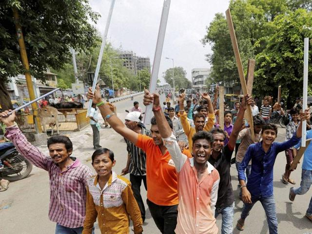 Dalit youths hold wooden sticks and shout slogans in Ahmedabad on Wednesday to protest the violence against four men from Dalit community for trying to skin a dead cow in Una town in Gujarat last week.