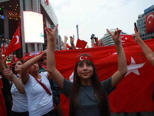 Pro Erdogan supporters wave Turkish flags during a rally at Kizilay Square in Ankara on Wednesday. Vienna has called Turkey's ambassador over concerns that Turkey is now developing increasingly authoritarian traits.