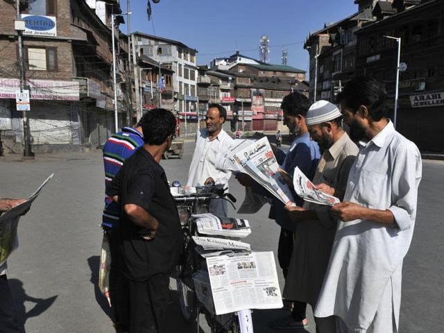 Kashmiri men read the morning newspaper at a newspaper store despite the curfew in Srinagar on Thursday. Newspapers hit the stands this morning in Kashmir after a gap of five days.