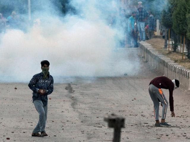 Kashmiri protesters throw stones after troops fired tear gas during clashes in Srinagar.